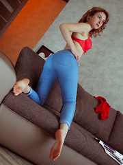 Redhead Jamie Joi strips on the sofa as she flaunts her sweet pussy.