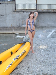 Wonderful long haired girl taking off swimsuit and showing shaved pussy in a yellow boat.