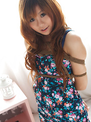 Apple Asian doll in cute dress and heels has hands tied in ropes